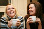 friends laughing and drinking coffee together