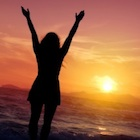 Resilient Woman at sunset with arms extended