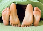 Lovers' feet in bed